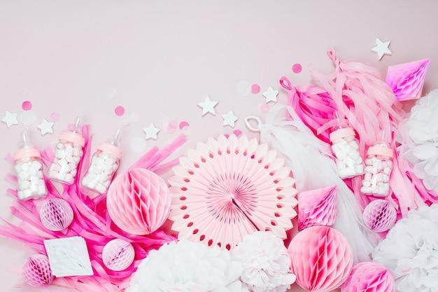 Roze en witte papieren decoraties voor baby shower party. het is een meisje. platliggend, bovenaanzicht