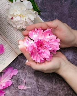 Roze en witte pioenrozen in een boeket op een grijze achtergrond roze pioenroos in open handpalmen op handen