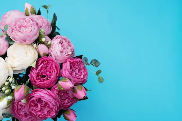 Roze en witte pione bloemen op blauwe achtergrond