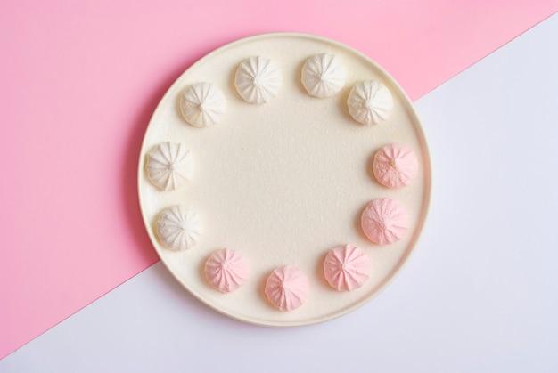 Roze en witte plaat met meringue zoete dessertkoekjes plat lag bovenaanzicht