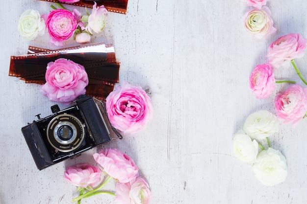 Roze en witte ranonkel verse bloeiende bloemen met retro camera plat leggen scène, kopie ruimte op houten bureaublad