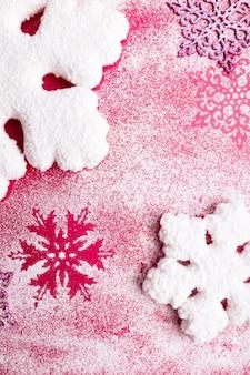 Roze en witte sneeuwvlokken op een roze achtergrond