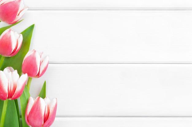 Roze en witte tulpen op een witte houten achtergrond.