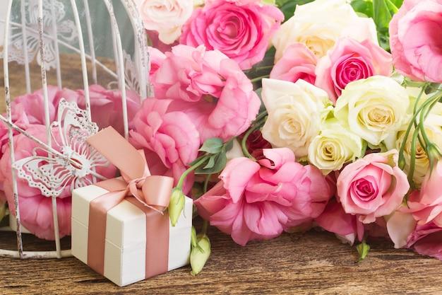 Roze en witte verse rozen en eustomabloemen met giftdoos op hout