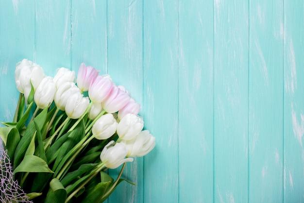 Roze en witte zeer tedere tulpen op groen blauwe houten achtergrond