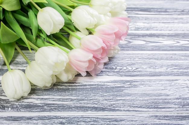 Roze en witte zeer zachte tulpen op witte, grijze houten achtergrond