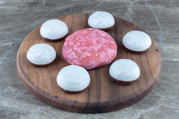 Roze en witte zelfgemaakte koekjes met houten plank.