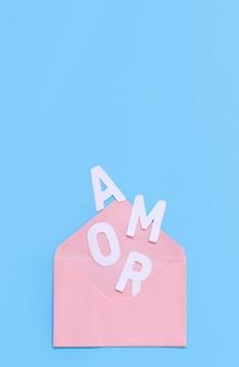 Roze envelop en tekst amor op een lichtblauwe achtergrond bovenaanzicht
