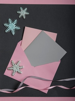 Roze envelop met ansichtkaarten, sneeuwvlokken en linten