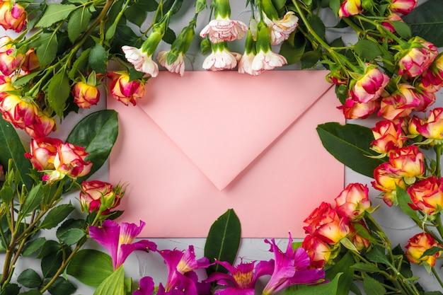 Roze envelop met bloemen, bovenaanzicht. romantische brief