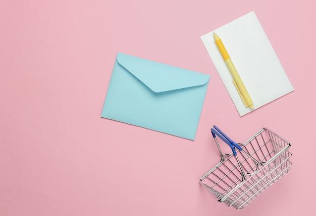 Roze envelop met brief en winkelmandje op roze pastel achtergrond. mockup voor valentijnsdag, bruiloft of verjaardag. bovenaanzicht