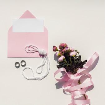 Roze envelop met bruiloft uitnodiging naast boeket rozen