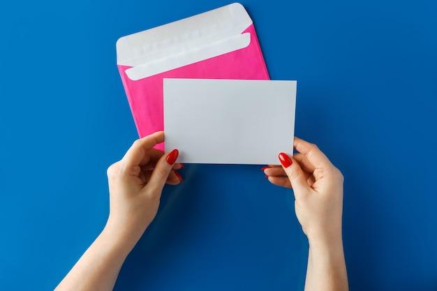Roze envelop met een lege kaart in handen op een blauwe achtergrond.