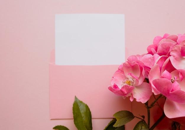 Roze envelop met een wit mockup-vel en een takje felroze roos ernaast op een roze achtergrond. sjabloon voor nieuwsbrieven en andere e-mailontwerpen.
