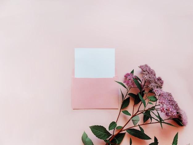 Roze envelop met een wit modelblad en roze bloemen ernaast op een roze achtergrondsjabloon voor