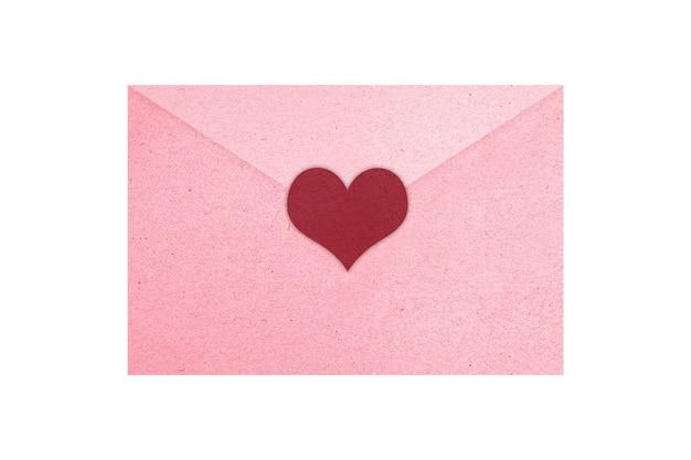 Roze envelop met hart dat over witte muur wordt geïsoleerd