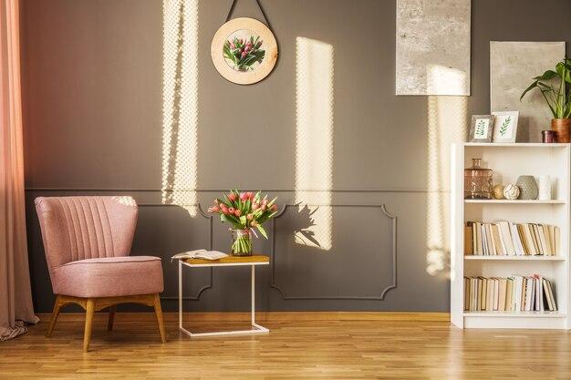 Roze fauteuil naast een tafel met rode tulpen in een gezellig grijs woonkamerinterieur met decor aan de muur