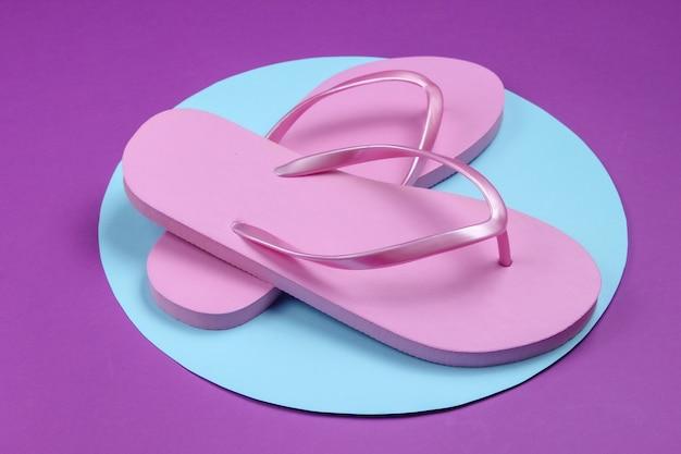 Roze flip-flops op paarse achtergrond met blauwe pastel cirkel. minimalistische vakantie op het strand-concept. zomertijd