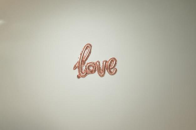Roze folie lucht inscriptie lucht folie ballon op een grijze achtergrond valentijnsdag