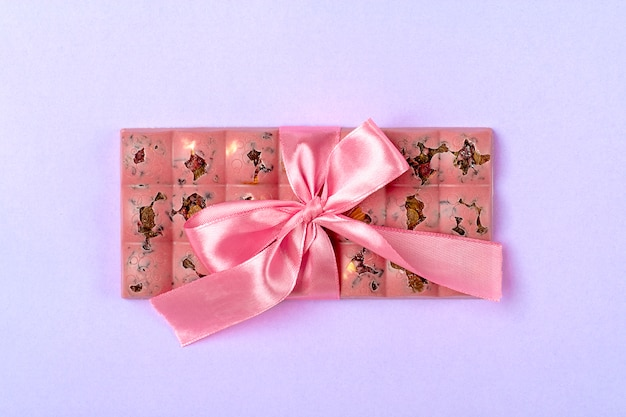 Roze fruit chocolade met rozijnen en noten geïsoleerd op lila kleur achtergrond dessert tijd concept candy shop