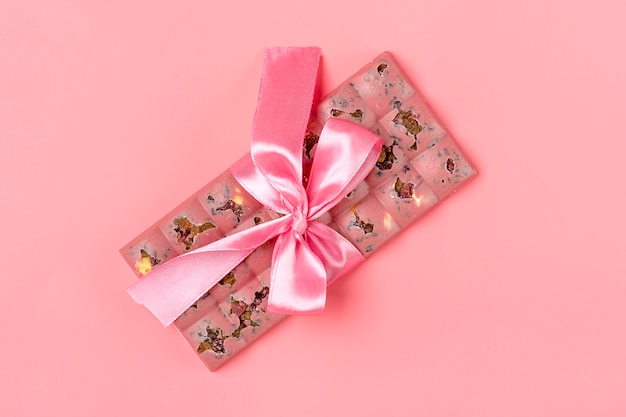 Roze fruitchocolade met rozijnen en noten die op het roze concept kleuren van de achtergronddesserttijd worden geïsoleerd
