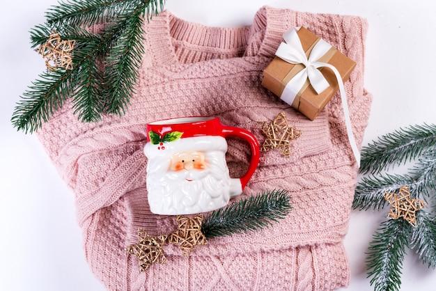 Roze gebreide trui met geschenkdoos, kerstmuts, kerstversiering en dennentakken, bovenaanzicht. kerstmisstilleven