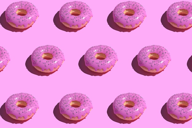 Roze geglazuurd donutpatroon op pastel.
