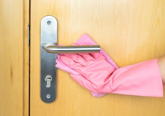Roze gehandschoende handreinigingsdeur. concept covid-19. kopieer ruimte.