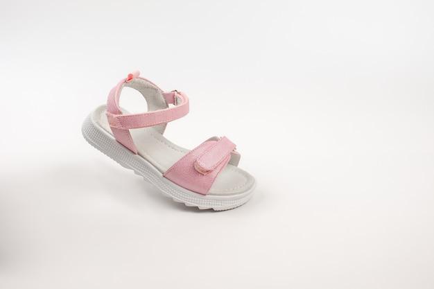 Roze geïsoleerde kindersandalen roze kindersandalen met witte zolen en klittenbandsluitingen geïsoleerd op een w...
