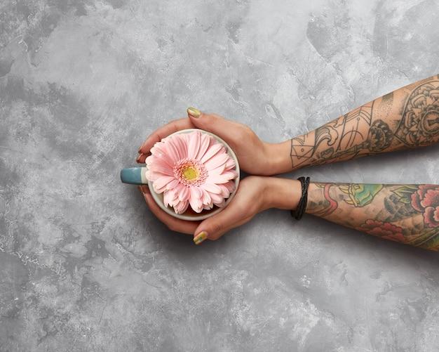 Roze gerbera in een kopje met thee, vrouw met een tatoeage houdt een kopje handen op een grijze betonnen ondergrond. het concept van de lente en een gelukkige ochtend. plat leggen.