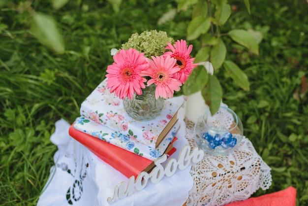 Roze gerbera's in een vaas die zich op een stapel boeken naast het woord in de russische taal bevinden
