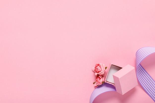 Roze geschenkdoos en bloemen op roze