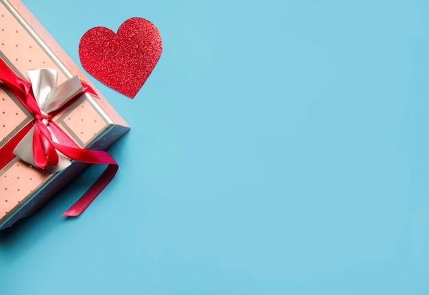 Roze geschenkdoos en rode harten op blauwe achtergrond