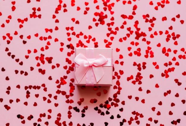 Roze geschenkdoos met holografische rode harten op pastel achtergrond. feestelijke achtergrond. bovenaanzicht.