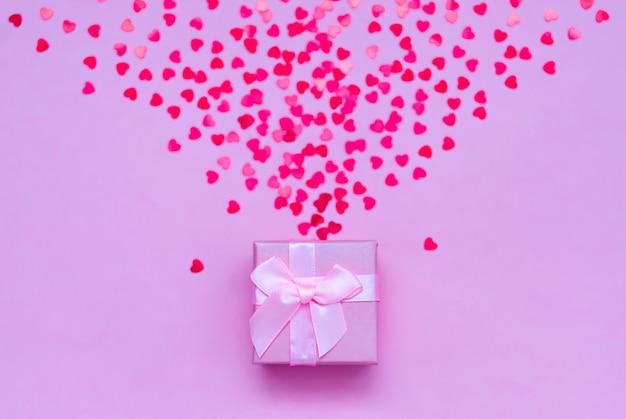 Roze geschenkdoos met holografische rode harten op pastel achtergrond.