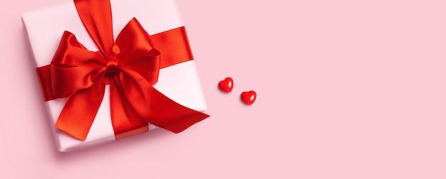 Roze geschenkdoos met rode strik en twee harten op roze achtergrond. bovenaanzicht. plat leggen.