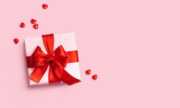 Roze geschenkdoos met rode strik op roze achtergrond met rode harten rond. bovenaanzicht. plat leggen.