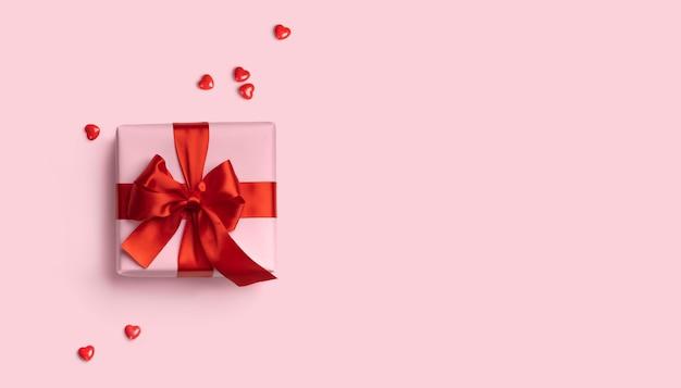 Roze geschenkdoos met rode strik op roze achtergrond met rode harten rond. vakantie webbanner. bovenaanzicht. plat leggen. ruimte kopiëren