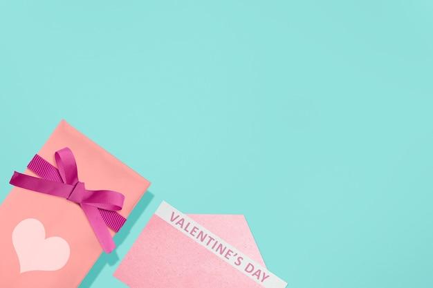 Roze geschenkdoos met rood lint en hart met geopende roze envelop met valentijnsdag tekst met een gekleurde achtergrond. valentijnsdag