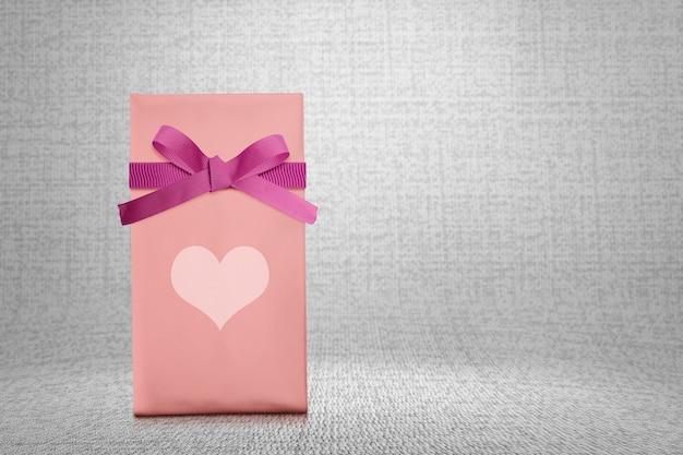Roze geschenkdoos met rood lint en hart met gestructureerde achtergrond