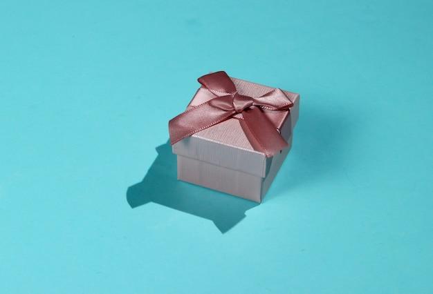 Roze geschenkdoos met strik op een blauwe pastel achtergrond close-up. vakantieconcept, verjaardag