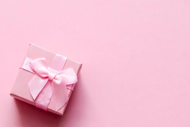 Roze geschenkdoos met strik op roze pastel achtergrond. feestelijke achtergrond. bovenaanzicht. ruimte kopiëren.