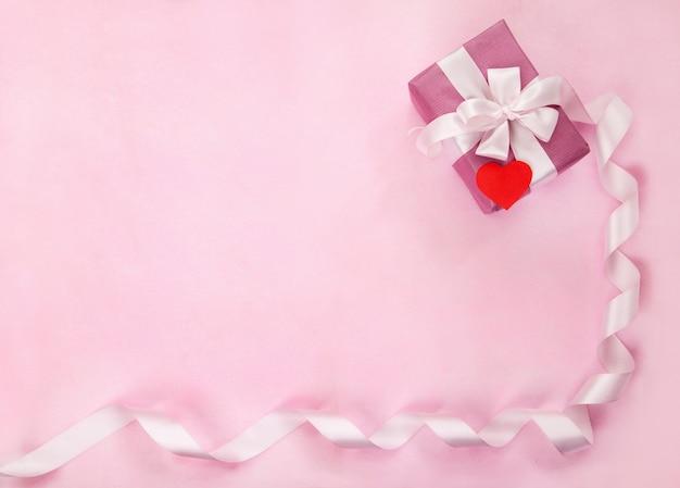 Roze geschenkdoos, witte strik, lang gebogen lint, papier rood hart. bovenaanzicht, plat gelegd. valentijnsdag