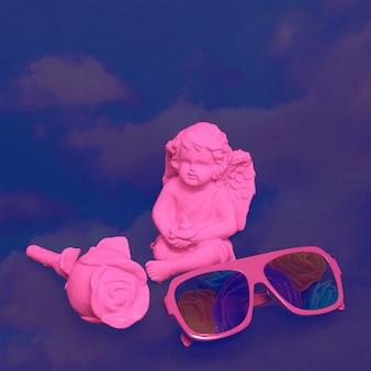 Roze geschilderde engel souvenir en rozen op zwarte achtergrond. stijlvolle zonnebril