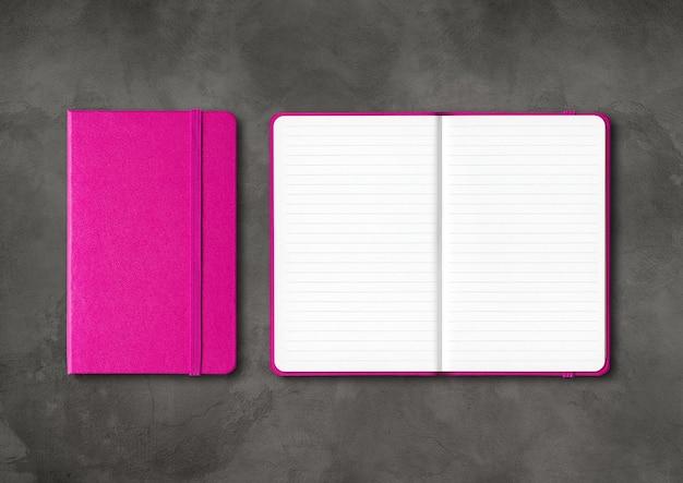 Roze gesloten en open beklede notebooks mockup geïsoleerd op donkere betonnen achtergrond