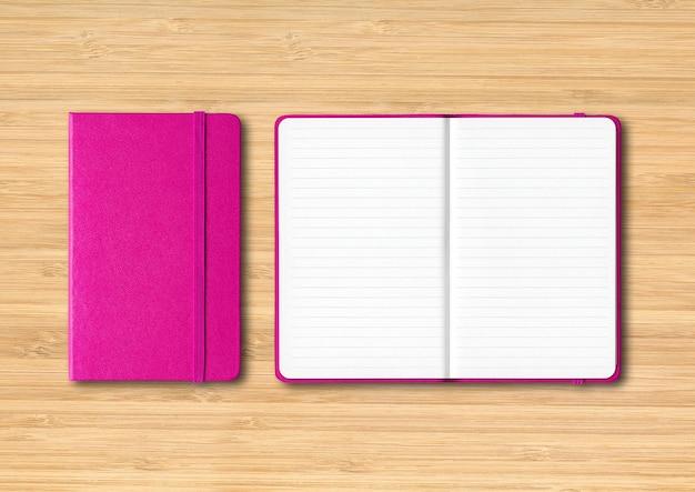 Roze gesloten en open bekleed notitieboekjemodel dat op houten achtergrond wordt geïsoleerd