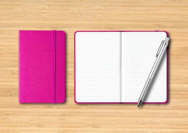 Roze gesloten en open gelinieerde notitieboekjes met een pen