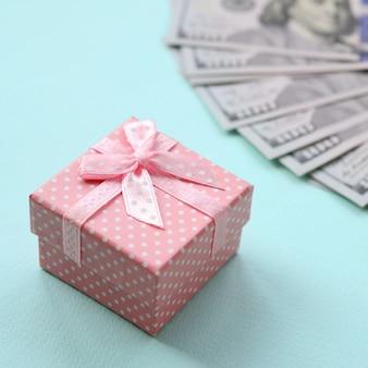 Roze gestippelde geschenkdoos ligt in de buurt van honderd dollarbiljetten op een lichtblauwe achtergrond