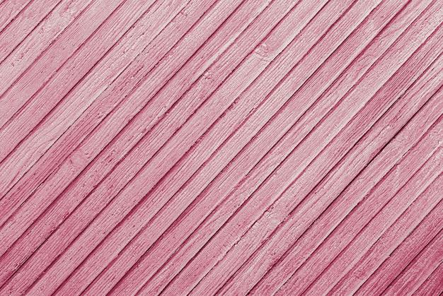 Roze gestructureerde achtergrond van diagonaal gerangschikte houten planken met gebarsten verf textuur