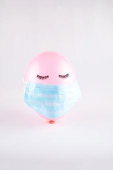 Roze gezichtsballon met zwarte wimpers gesloten ogen met gezichtsbeschermend masker. covid-19 concept. minimaal concept